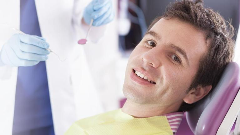 Man sitting in dental chair smiling l Root Canal Royal Oak MI
